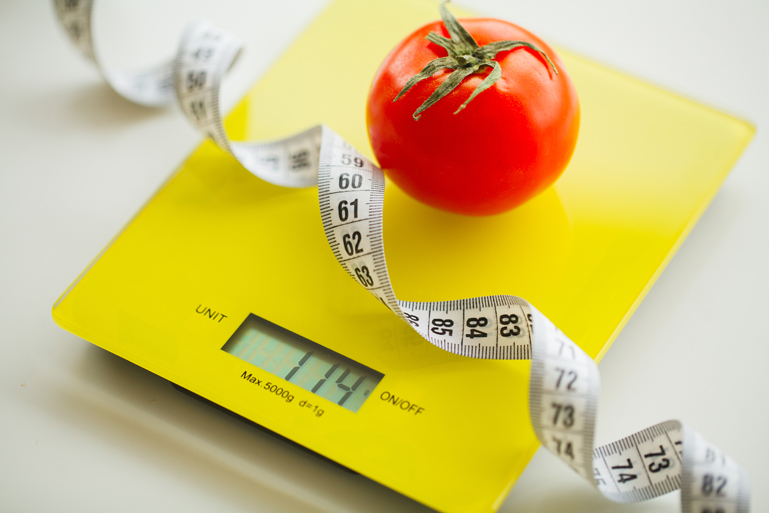 Diet. Tomato with measuring tape on weight scale